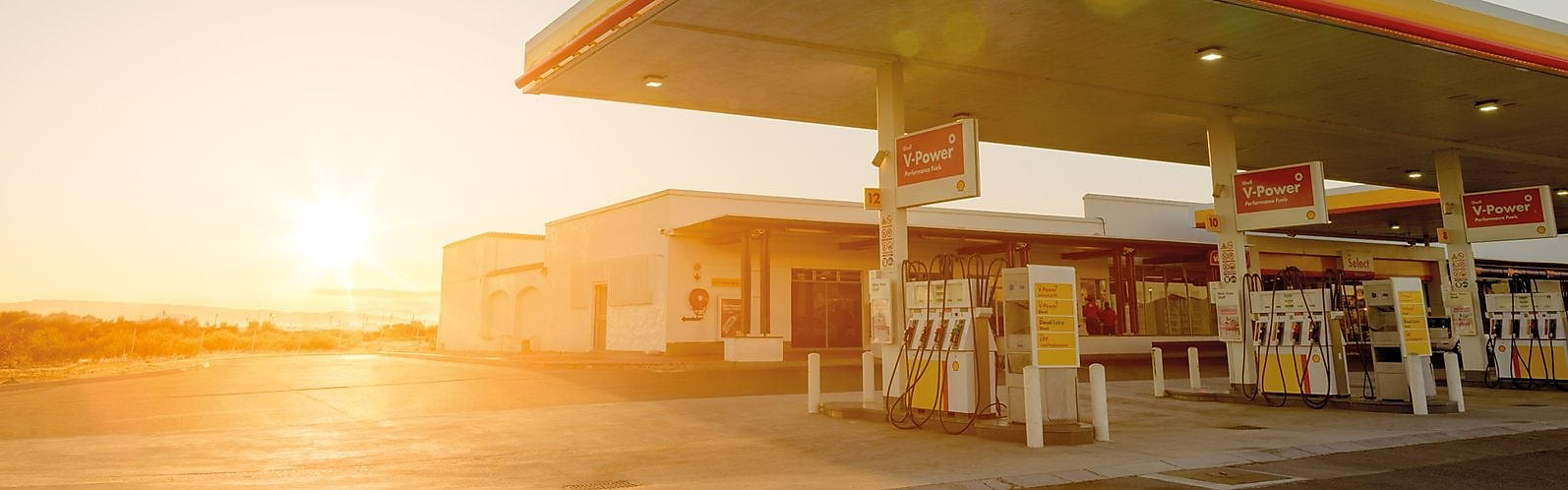 Sun rising behind a Shell station forecourt
