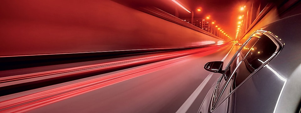 Car driving in a tunnel with light trails