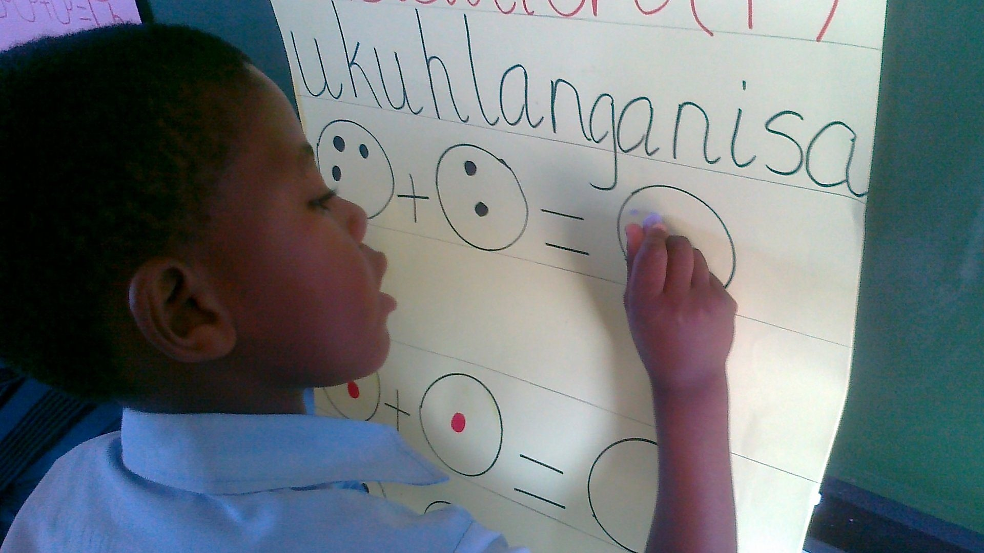 Child solving problem at flip chart