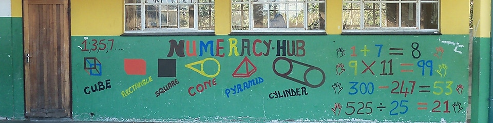 Outside maths school building with colourful walls and sums written on walls